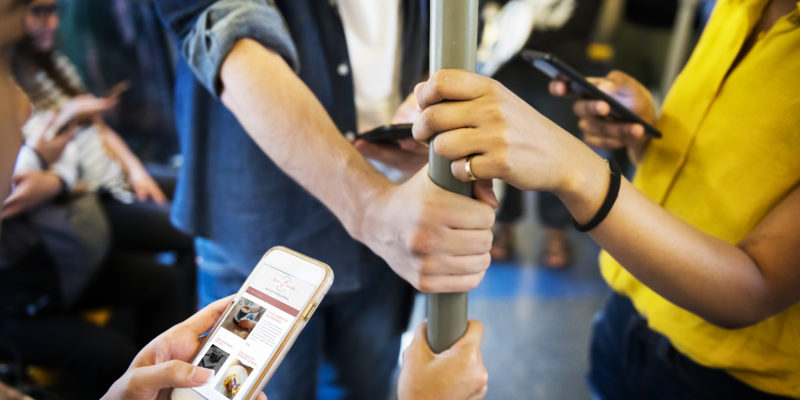 Group of young investors using app on the subway